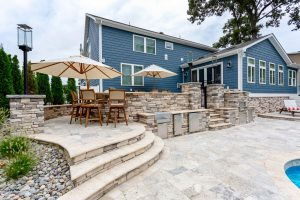 Custom outdoor grill and pizza oven in backyard makeover by Ashton Group at the Beach in Rehoboth Beach, Delaware.