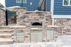 Custom outdoor kitchen with pizza oven in Rehoboth Beach, Delaware.